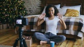 Jonge vrolijke gemengde de opname videoblog van het rasmeisje over de giftdoos van verpakkingskerstmis thuis royalty-vrije stock fotografie