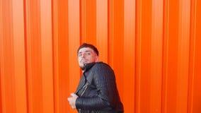 Jonge vrolijke Kaukasische kerel met een baard die rond en op camera, oranje aantrekkelijke achtergrond voor de gek houden vechte stock footage