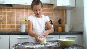Jonge vrolijke meisjes die deeg op donkere lijst in keuken kneden stock videobeelden
