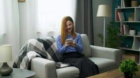 Jonge vrolijke meisjeszitting op bank met een smartphone in haar comfortabele woonkamer stock video