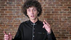 Jonge vrolijke mens met krullend haar die en zijn vingers benadrukken, bakstenen muurachtergrond dansen stock videobeelden
