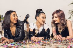 jonge vrolijke multi-etnische meisjes die op vloer met glazen liggen stock afbeeldingen