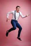 Jonge vrolijke stylishly geklede mens in een sprong Stock Fotografie