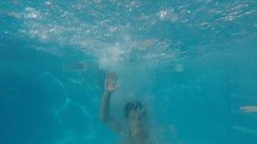Jonge vrolijke vrienden die, ontspannen, die in zwembad springen glimlachen stock footage