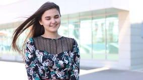 Jonge vrolijke vrouw die en in winderige dag knipogen glimlachen stock video