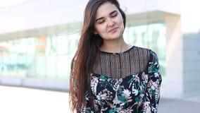Jonge vrolijke vrouw die en in winderige dag knipogen glimlachen stock videobeelden