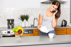 Jonge vrolijke vrouw die op de telefoon in keuken spreken Royalty-vrije Stock Afbeeldingen