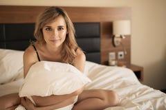 Jonge vrolijke vrouw die in slaapkamer glimlachen stock afbeeldingen