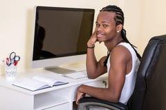 Jonge vrolijke zwarte mens bij computer Stock Afbeelding