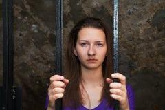 Jonge vrouw achter de staven Royalty-vrije Stock Afbeelding