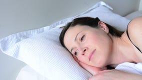 Jonge vrouw alleen in bedontwaken gelukkig in bed stock footage