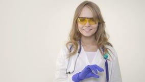 Jonge vrouw arts die en spuit op witte achtergrond glimlachen houden stock video