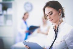 Jonge vrouw arts die zich bij het ziekenhuis met medische stethoscoop bevinden Stock Fotografie