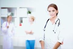 Jonge vrouw arts die zich bij het ziekenhuis met medische stethoscoop bevinden Stock Afbeeldingen