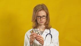 Jonge vrouw arts Gele achtergrond Het concept Geneeskunde stock videobeelden