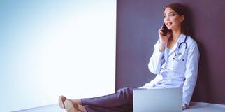 Jonge vrouw artsenzitting met uw telefoon Stock Fotografie