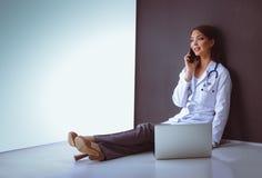 Jonge vrouw artsenzitting met uw telefoon Royalty-vrije Stock Foto's