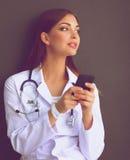Jonge vrouw artsenzitting op de vloer met uw telefoon Stock Foto