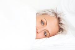 Jonge vrouw in bed onder deken Stock Foto