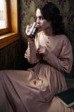 Jonge vrouw in beige uitstekende kleding van vroeg - Th-20 eeuw drinkin royalty-vrije stock foto's