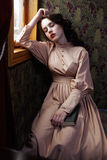 Jonge vrouw in beige uitstekende kleding van vroeg - Th-20 eeuw sleapin Royalty-vrije Stock Foto's