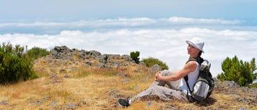 Jonge vrouw in bergen boven de wolken Royalty-vrije Stock Afbeelding