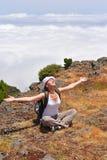 Jonge vrouw in bergen boven de wolken Royalty-vrije Stock Foto