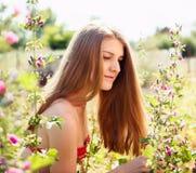 Jonge vrouw bij aard, die door wilde mallows omringen Royalty-vrije Stock Afbeeldingen
