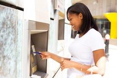 Jonge vrouw bij ATM stock foto