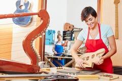 Jonge vrouw bij de leertijd van de gitaarmaker stock foto