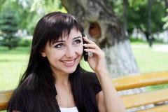 Jonge vrouw bij de lentepark die op de telefoon spreken. royalty-vrije stock afbeelding