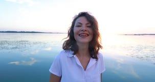 Jonge vrouw bij de pijler door de rivier bij zonsondergang stock videobeelden