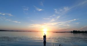 Jonge vrouw bij de pijler door de rivier bij zonsondergang stock footage