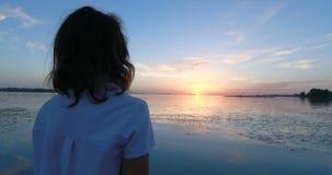 Jonge vrouw bij de pijler door de rivier bij zonsondergang stock video