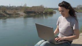 Jonge vrouw bij de rivier met laptop Het meisje zit met laptop op de rivierbank Een de lente zonnige dag op de waterkant stock videobeelden