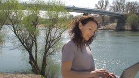 Jonge vrouw bij de rivier met laptop Het meisje zit met laptop op de rivierbank Een de lente zonnige dag op de waterkant stock footage