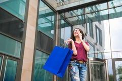 Jonge vrouw bij de straat met het winkelen zak die op mobiele telefoon spreken stock foto