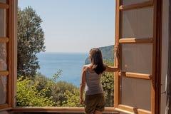 Jonge vrouw bij een groot open venster royalty-vrije stock afbeeldingen
