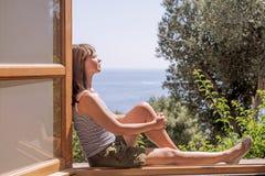 Jonge vrouw bij een groot open venster De zomer abstracte foto stock afbeeldingen