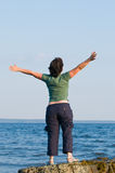 Jonge vrouw bij het strand met uitgestrekte wapens Stock Foto's