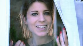 Jonge vrouw bij het venster stock videobeelden