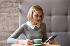 Jonge vrouw bij koffie het drinken koffie en het gebruiken van mobiele telefoon Royalty-vrije Stock Foto