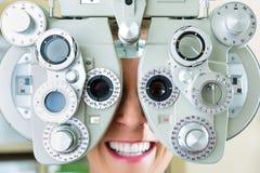 Jonge vrouw bij phoropter voor oogtest stock afbeelding