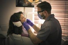 Jonge vrouw bij tandartsonderzoek Stock Foto's