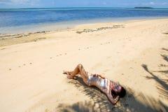 Jonge vrouw in bikini die op het strand op Makaha ` dichtbij liggen een eiland Royalty-vrije Stock Afbeeldingen