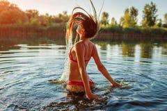 Jonge vrouw in bikini die uit water springen en plons maken De vakantie van de zomer royalty-vrije stock afbeelding