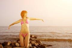 Jonge vrouw in bikini op strand met omhoog haar zijn handen Meisje met Stock Afbeeldingen