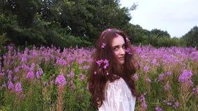 Jonge vrouw in bloemen stock videobeelden