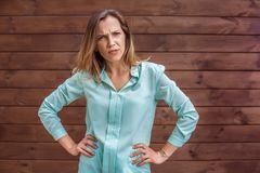 Jonge vrouw in blouse die op muurhanden wordt zich geïsoleerd bevinden die op boze heupen royalty-vrije stock foto's