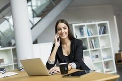 Jonge vrouw in bureau royalty-vrije stock afbeelding
